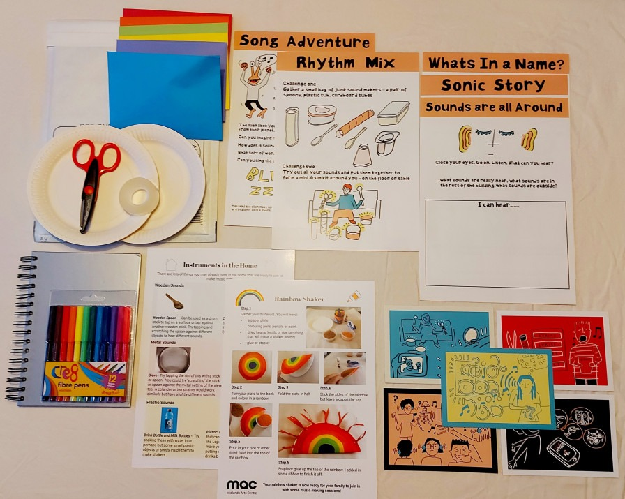 This photo shows the content of activity packs. It includes 7 A4 worksheets, 5 postcards, paper plates, scissors, tape, pens, and coloured envelopes laid out on a white table cloth.