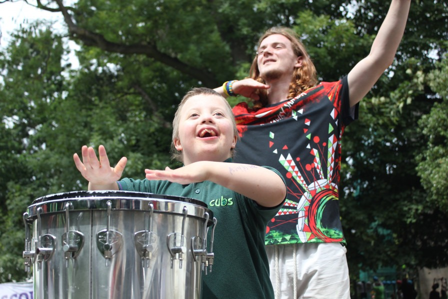 A young boy playing a drum with a teenager in the background waving their arms