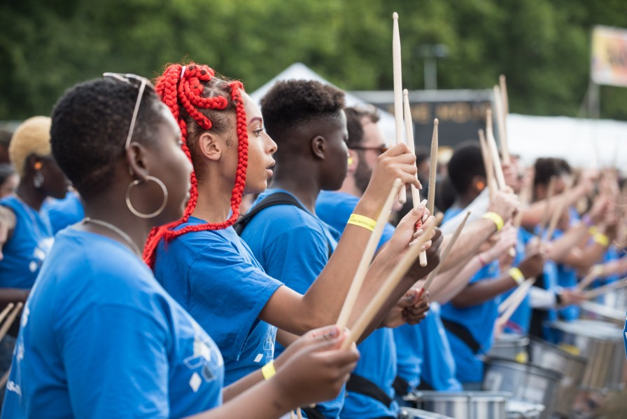 Young people from the Drumworks Exchanging Notes project performing outside.