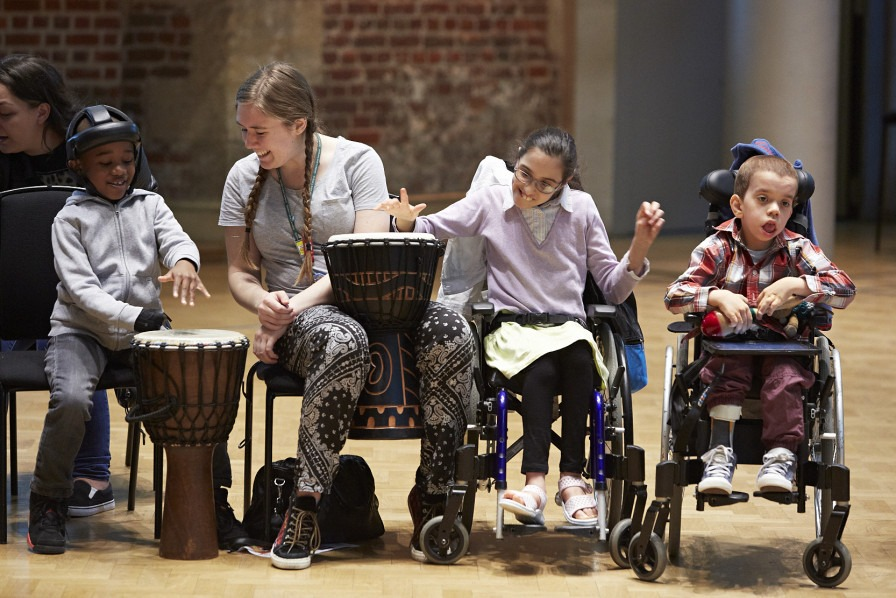 Music leader making music with three young people, two of whom are wheelchair-users. Two of the young people are playing African drums, the third young person is playing the maracas.