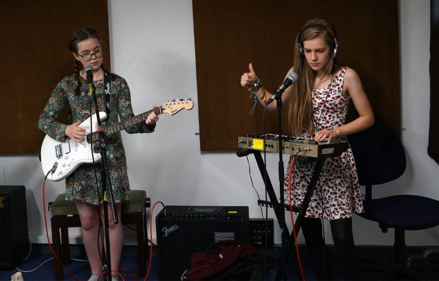 Young person with a guitar and young person with a keyboard
