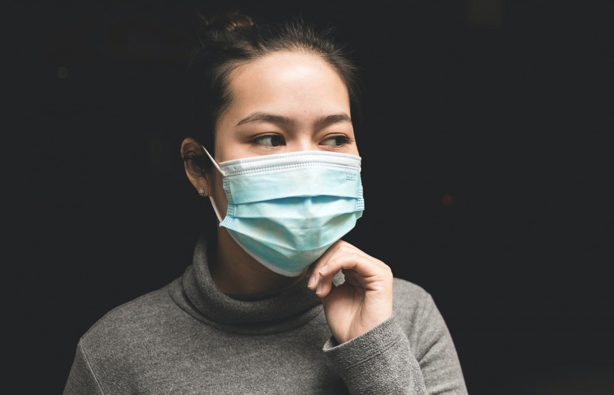 Head and shoulders of a woman with a face mask on. Photo taken by Michael Amadeus on Unsplash.