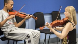 Music Leader with Young Participant, playing violin