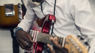 Close up of young man playing guitar at MYA Noise Project